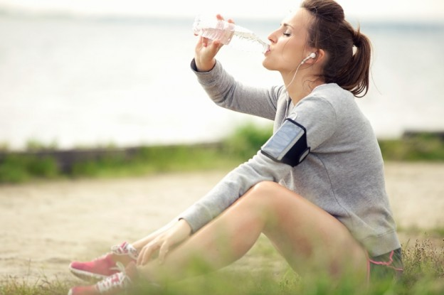 Tired female jogger sitting on the grass and drinking bottled water